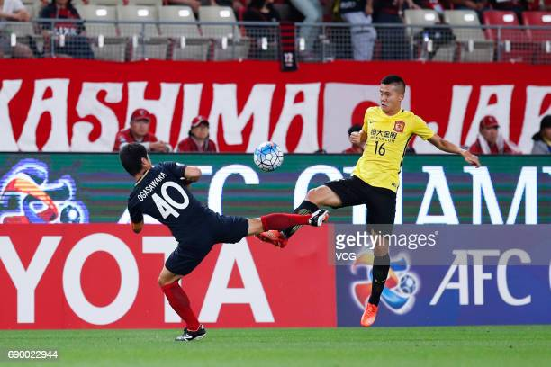 Huang Bowen of Guangzhou Evergrande and Mitsuo Ogasawara of Kashima Antlers vie for the ball during the AFC Champions League Round of 16 match...