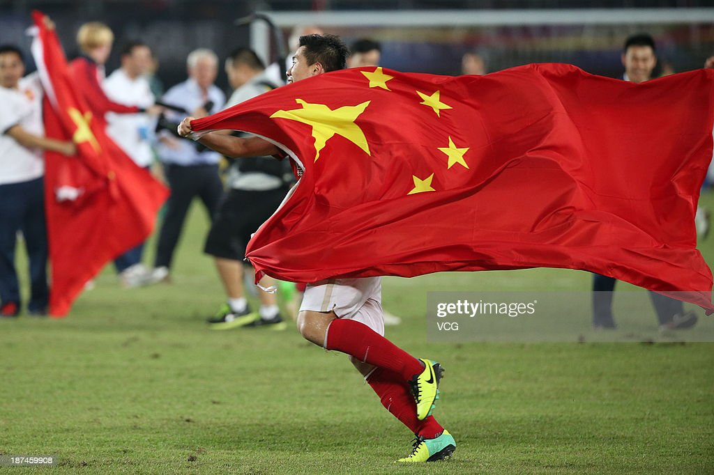 Huang Bowen #16 of Guangzhou Evergrande celebrates with a Chinese flag after winning the AFC Champions League Final 2nd leg match against FC Seoul at Tianhe Sports Center on November 9, 2013 in Guangzhou, China.