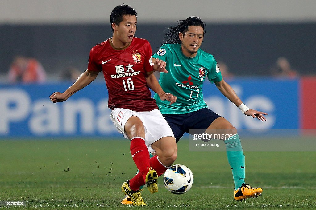 Huang Bowen of Guangzhou Evergrande challenges Mitsuru Nagata of Urawa Red Diamonds during the AFC Champions League Group F match between Guangzhou Evergrande and Urawa Red Diamonds at Tianhe Stadium on February 26, 2013 in Guangzhou, China.