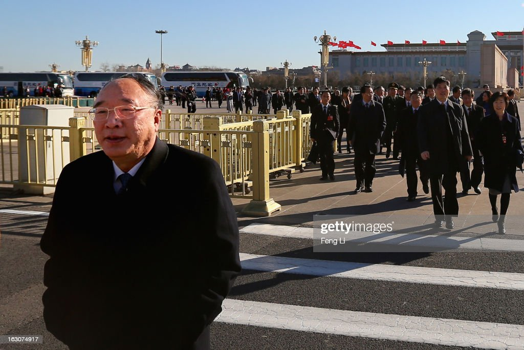 Huang Qifan (L), Chongqing Mayor and delegate of the National People's Congress, walks from Tiananmen Square to the Great Hall of the People to attend a pre-opening session of the National People's Congress, China's parliament, on March 4, 2013 in Beijing, China. Over 2,000 members of the 12th National Committee of the Chinese People's Political Consultative, a political advisory body, are attending the annual session, during which they will discuss the development of China.