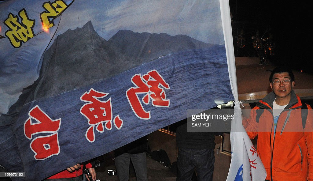 Huang Xilin, a Taiwan right-wing activist, displays a Diaoyu islands flag at the Sheng Ao fish harbour in northern city of Keelung on January 24, 2013. A boat with Taiwanese activists headed for disputed Japanese-controlled islands turned back after coastguard vessels from the two sides converged and duelled with water cannon. AFP PHOTO / Sam Yeh