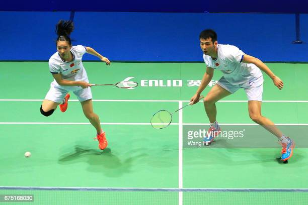 Huang Yaqiong of China hits a return next to her partner Lu Kai during their mixed doubles final match against Sapsiree Taerattanachaiachai and...