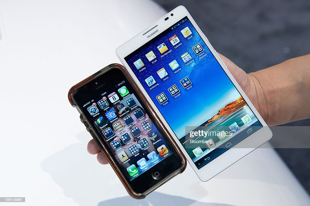 A Huawei Technologies Co. Ascend Mate smartphone, right, and an Apple Inc. iPhone 5 are arranged for a photograph at the 2013 Consumer Electronics Show in Las Vegas, Nevada, U.S., on Tuesday, Jan. 8, 2013. The 2013 CES trade show, which runs until Jan. 11, is the world's largest annual innovation event that offers an array of entrepreneur focused exhibits, events and conference sessions for technology entrepreneurs. Photographer: David Paul Morris/Bloomberg via Getty Images