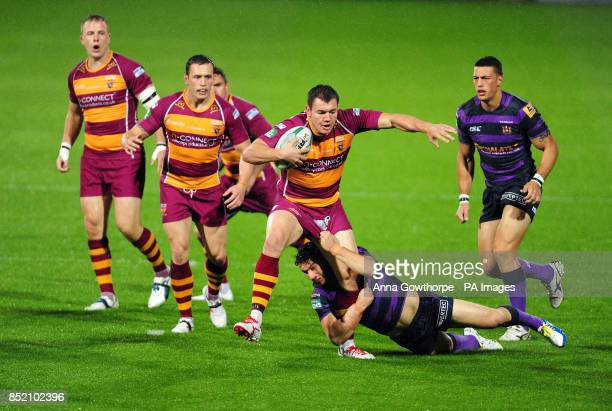 Huddersfield Giants' Brett Ferres is tackled by Wigan Warriors' Matthew Smith during the Super League Elimination Play Off at the John Smith's...