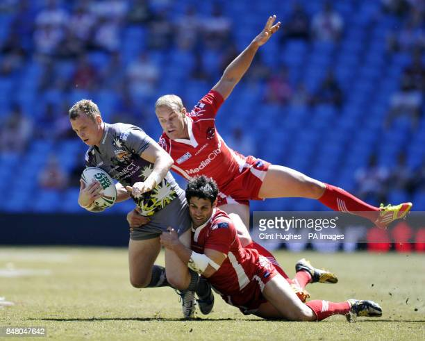 Huddersfield Giants's Kevin Brown is tackled by Salford City Reds's Chris Nero and Daniel Holdsworth during the Stobart Super League Magic Weekend...