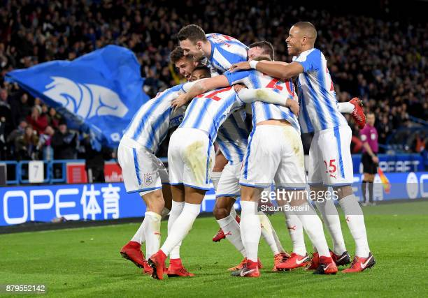 Huddersfield players celebrate after Nicolas Otamendi of Manchester City scored the first own goal during the Premier League match between...