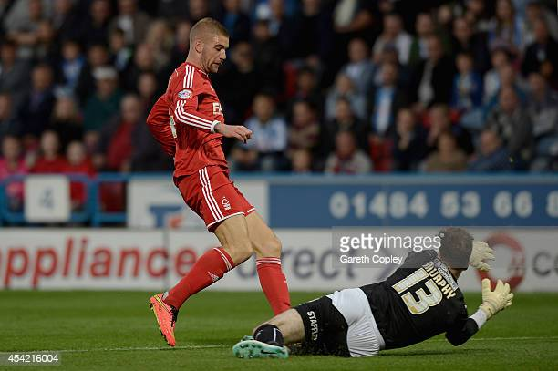 Huddersfield Town goalkeeper Joe Murphy saves from the feet of Lars Veldwijk of Nottingham Forest during the Capital One Cup Second Round match...