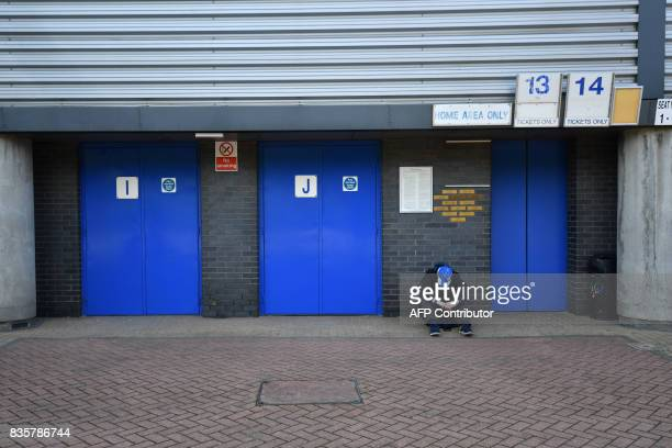 A Huddersfield Town supporter waits outside the stadium prior to the start of the English Premier League football match between Huddersfield Town and...