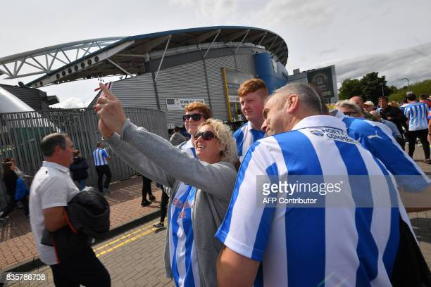 Huddersfield Town supporters gather outside the stadium prior to the start of the English Premier League football match between Huddersfield Town and...