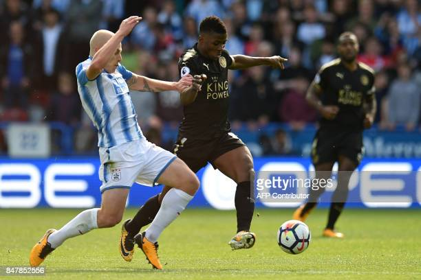 Huddersfield Town's Australian midfielder Aaron Mooy vies with Leicester City's Nigerian striker Kelechi Iheanacho during the English Premier League...