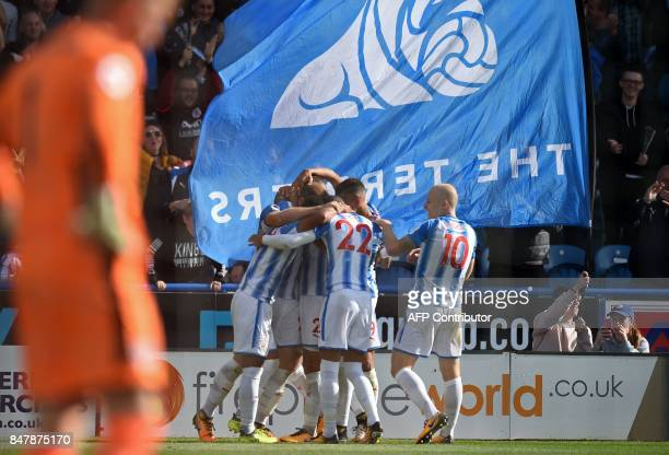 Huddersfield Town's Belgian striker Laurent Depoitre celebrates with teammates after scoring the opening goal of the English Premier League football...
