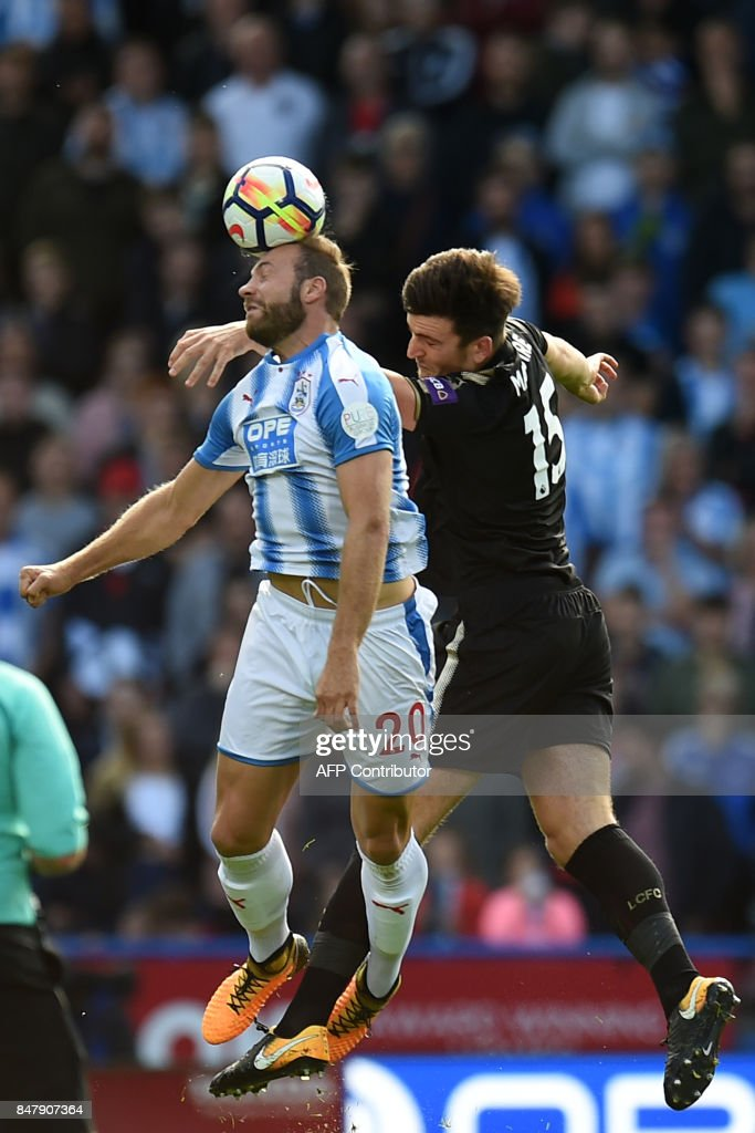 Huddersfield Town's Belgian striker Laurent Depoitre (L) vies with Leicester City's English defender Harry Maguire during the English Premier League football match between Huddersfield Town and Leicester City at the John Smith's stadium in Huddersfield, northern England on September 16, 2017. The game finished 1-1. / AFP PHOTO / Oli SCARFF / RESTRICTED TO EDITORIAL USE. No use with unauthorized audio, video, data, fixture lists, club/league logos or 'live' services. Online in-match use limited to 75 images, no video emulation. No use in betting, games or single club/league/player publications. /