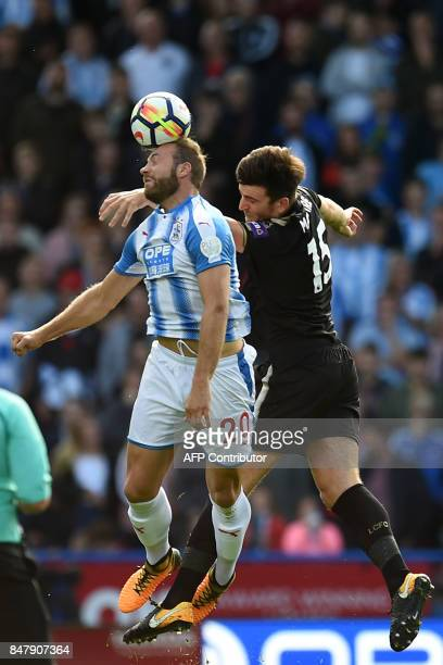 Huddersfield Town's Belgian striker Laurent Depoitre vies with Leicester City's English defender Harry Maguire during the English Premier League...