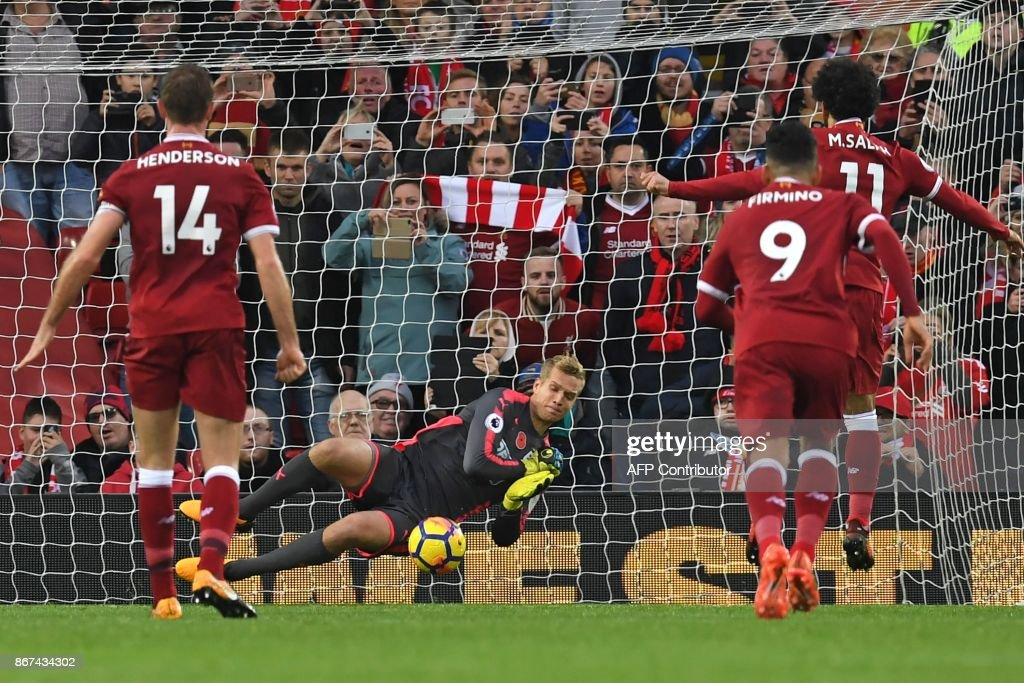 Huddersfield Town's Danish goalkeeper Jonas Lossl (C) saves a penalty from Liverpool's Egyptian midfielder Mohamed Salah (R) during the English Premier League football match between Liverpool and Huddersfield Town at Anfield in Liverpool, north west England on October 28, 2017. / AFP PHOTO / Paul ELLIS / RESTRICTED TO EDITORIAL USE. No use with unauthorized audio, video, data, fixture lists, club/league logos or 'live' services. Online in-match use limited to 75 images, no video emulation. No use in betting, games or single club/league/player publications. /
