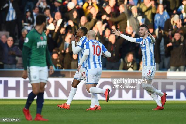 Huddersfield Town's Dutch midfielder Rajiv van La Parra celebrates after scoring with Huddersfield Town's Australian midfielder Aaron Mooy during the...