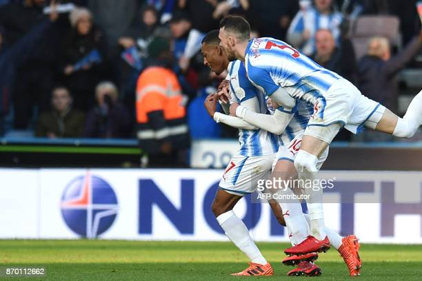 Huddersfield Town's Dutch midfielder Rajiv van La Parra celebrates after scoring with Huddersfield Town's Australian midfielder Aaron Mooy and...