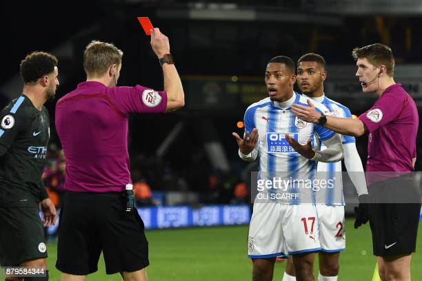 Huddersfield Town's Dutch midfielder Rajiv van La Parra is shown a red card by English referee Craig Pawson at the end of the English Premier League...
