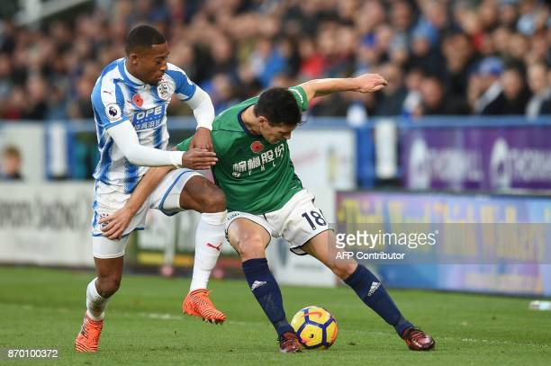 Huddersfield Town's Dutch midfielder Rajiv van La Parra vies with West Bromwich Albion's English midfielder Gareth Barry during the English Premier...