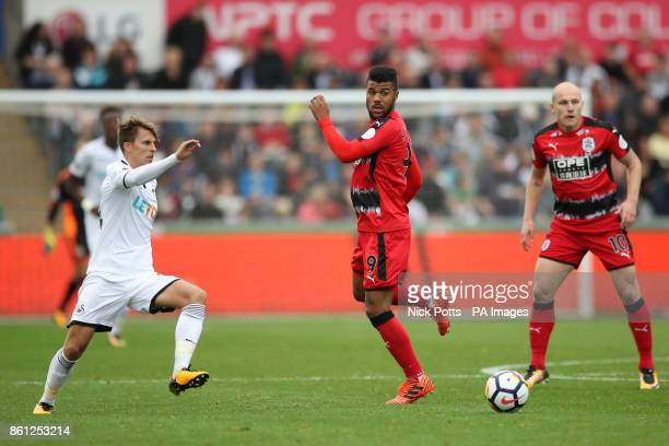 Huddersfield Town's Elias Kachunga and Swansea City's Tom Carroll battle for the ball during the Premier League match at the Liberty Stadium Swansea