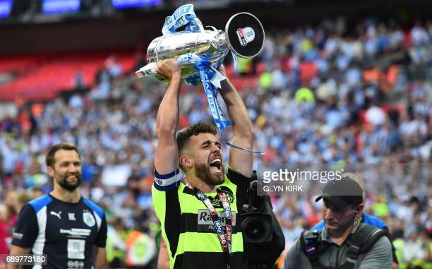 Huddersfield Town's English defender Tommy Smith holds up the Championship Playoff trophy as Huddersfield's players celebrate winning the penalty...