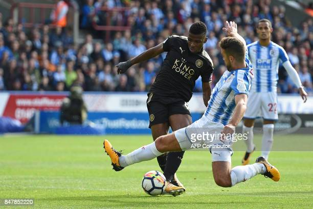 Huddersfield Town's English defender Tommy Smith leaps in to block a shot from Leicester City's Nigerian striker Kelechi Iheanacho during the English...