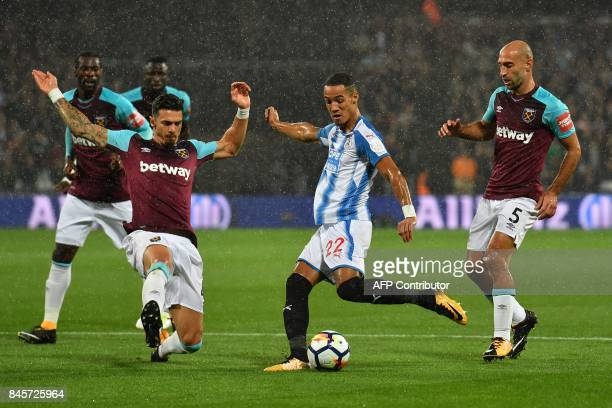 Huddersfield Town's English midfielder Tom Ince has a shot on goal during the English Premier League football match between West Ham United and...