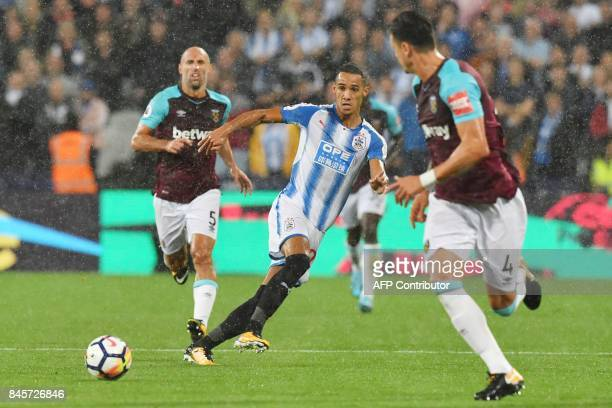 Huddersfield Town's English midfielder Tom Ince vies with West Ham United's Portuguese defender Jose Fonte during the English Premier League football...