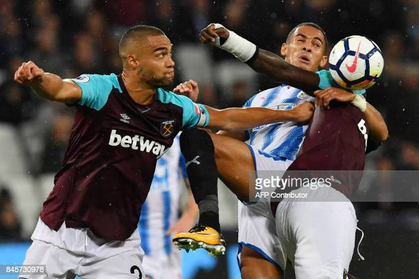 Huddersfield Town's English midfielder Tom Ince vies with West Ham United's New Zealand defender Winston Reid and West Ham United's Senegalese...