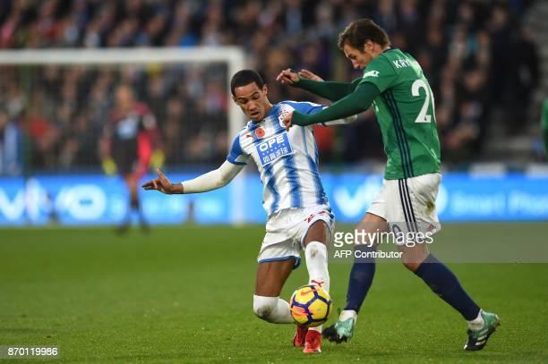 Huddersfield Town's English midfielder Tom Ince vies with West Bromwich Albion's Polish midfielder Grzegorz Krychowiak during the English Premier...