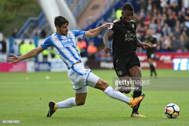Huddersfield Town's German defender Christopher Schindler is booked for this challenge on Leicester City's Nigerian striker Kelechi Iheanacho during...