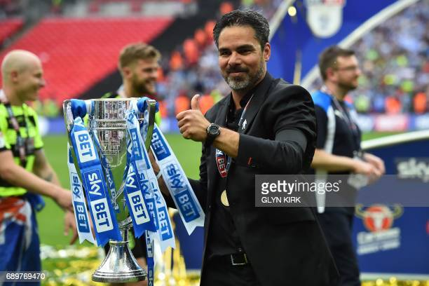 Huddersfield Town's German head coach David Wagner gestures as he holds the Championship Playoff trophy on the pitch after winning the penalty...