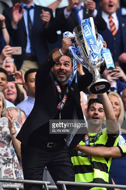 Huddersfield Town's German head coach David Wagner lifts the Championship Playoff trophy as his players celebrate winning the penalty shootout in the...