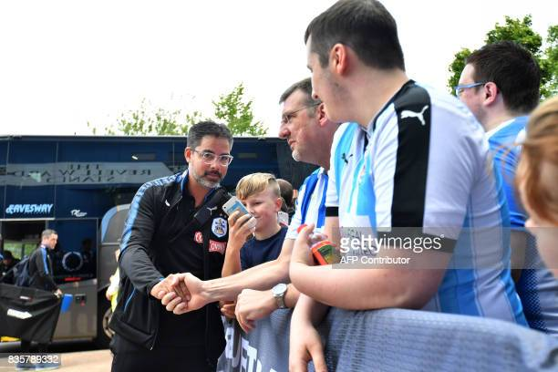 Huddersfield Town's German head coach David Wagner poses with a young supporter on his arrival at the stadium prior to the start of the English...