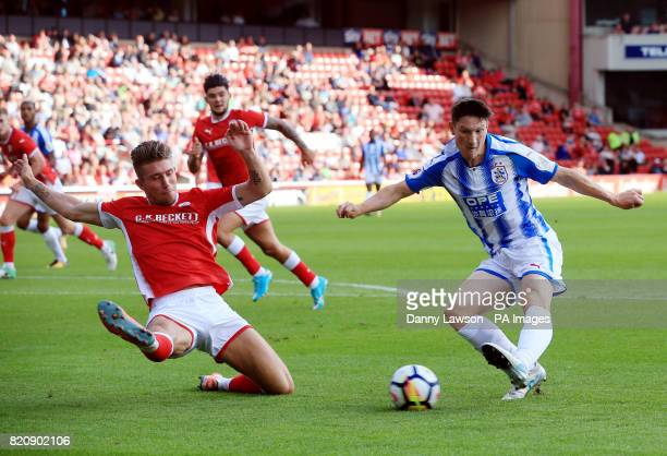 Huddersfield Town's Joe Lolley and Barnsley FC's Angus MacDonald battle for the ball during the preseason friendly match at Oakwell Barnsley