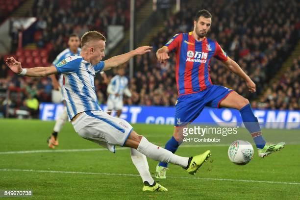 Huddersfield Town's Swiss defender Florent Hadergjonaj crosses the ball during the English League Cup third round football match between Crystal...