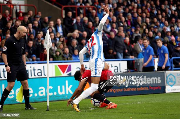 Huddersfield Town's Tom Ince climbs over Manchester United's Jesse Lingard as he tries to tackle him during the Premier League match at the John...