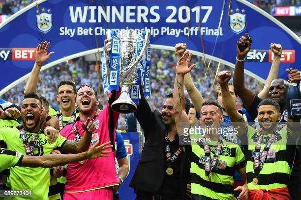 Huddersfield Town's Welsh goalkeeper Danny Ward and Huddersfield Town's German head coach David Wagner hold up the Championship Playoff trophy as...