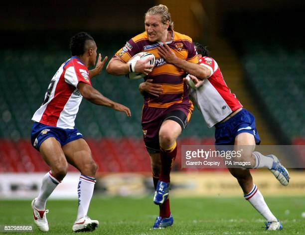 Huddersfield's Eorl Crabtree is tackled by Wakefield's Paul White and Ben Jefferies during the Engage Super League match at the Millennium Stadium...