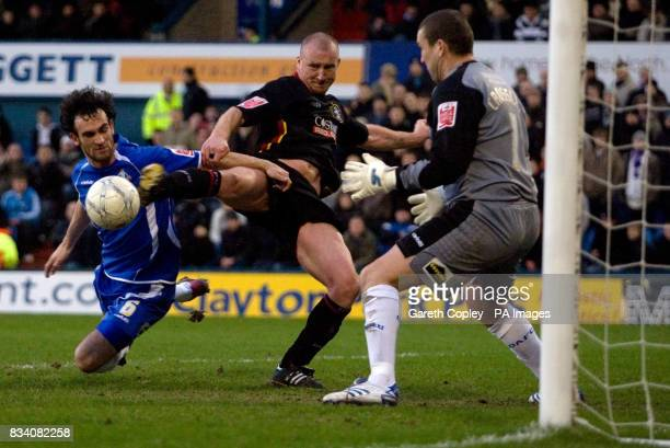 Huddersfield's Luke Beckett tries to get a shot away despite tackles from Oldham's Stefan Stam and Mark Crossley during the FA Cup Fourth Round match...