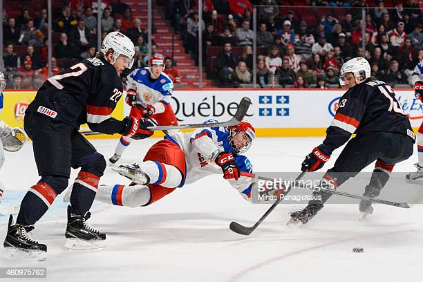 Hudson Fasching of Team United States trips Ivan Provorov of Team Russia in a quarterfinal round during the 2015 IIHF World Junior Hockey...