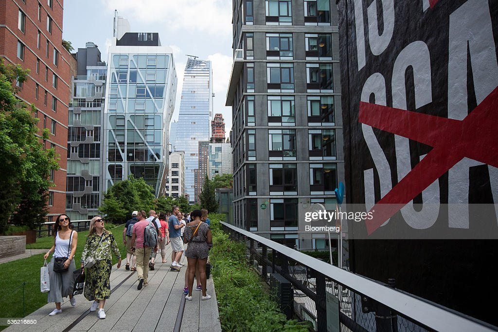 10 Hudson Yards, center, home to Coach Inc.'s new offices, stands as pedestrians walk on the Highline in New York, U.S., on Tuesday, May 31, 2016. The first skyscraper at Related Cos.'s $25 billion Hudson Yards project opened Tuesday after three and a half years of construction, bringing office workers to a once-desolate area of Manhattan's far west side that's now transforming into a new business enclave. Photographer: Michael Nagle/Bloomberg via Getty Images