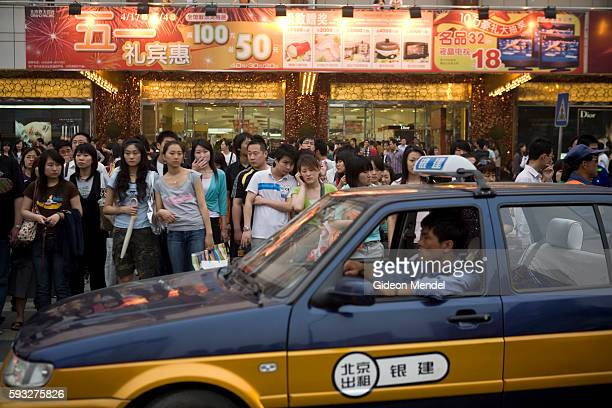 A huge amount of pedestrians wait to cross a busy intersection in the Xidan shopping area during the Mayday holiday break Shopping is one of the most...