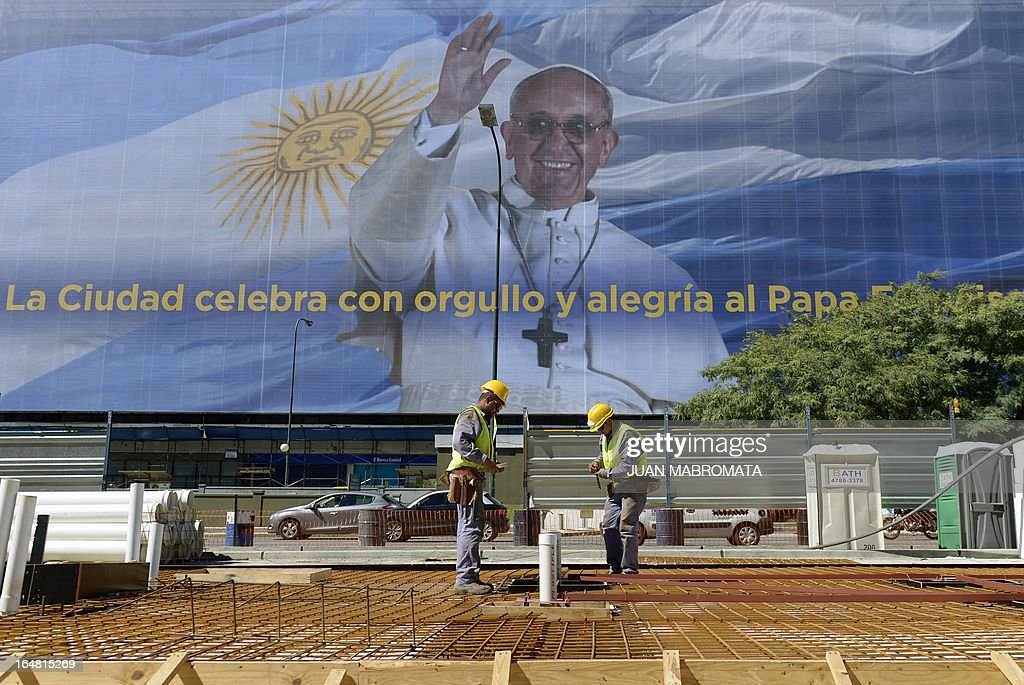A huge banner depicting Pope Francis backgrounded by the Argentinian flag and an inscription that reads 'The city celebrates with pride and joy Pope Francis' can be seen covering the facade of a building while men work on a Metrobus stop along 9 de Julio Avenue in Buenos Aires on March 28, 2013. AFP PHOTO/Juan Mabromata