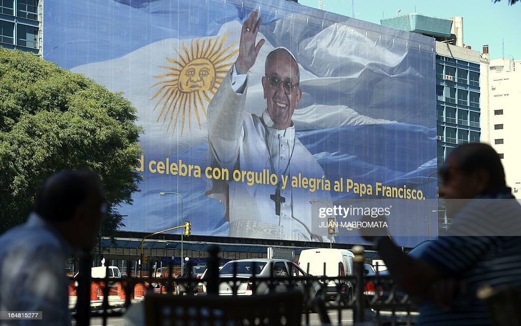 A huge banner depicting Pope Francis backgrounded by the Argentinian flag and an inscription that reads 'The city celebrates with pride and joy Pope Francis' can be seen covering the facade of a building along 9 de Julio Avenue in Buenos Aires on March 28, 2013. AFP PHOTO/Juan Mabromata