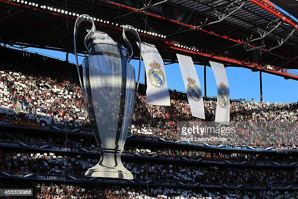 A huge banner of the Champions League trophy is unfurled in the stadium alongside banners of the Real Madrid logo prior to the UEFA Champions League...