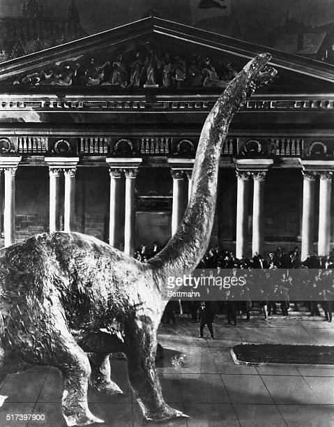 A huge brontosaurus threatens a crowd of Londoners outside a Neoclassical building in a still from the 1925 film version of Conan Doyle's The Lost...