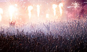 Cheering crowd at concert in front of stage with pyrotechnics