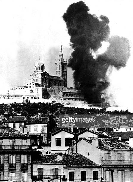 A huge column of black smoke rises from the Basilique NotreDame de La Garde as German troops shell Marseille after the Allied troops entered the town...