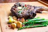 Large cowboy cut bone-in rib eye steak grilled up and on a plate with Brussels sprouts and Asparagus, a perfect ketogenic or low carb diet meal.