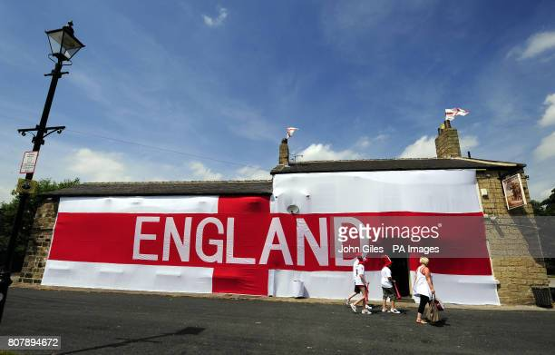 A huge cross of St George on the wall of the Cricketers Pub in Seacroft Leeds as England supporters make their way inside for the World Cup Match...
